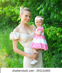 Portrait of happy young mother and baby daughter wearing a dress together having fun in summer day