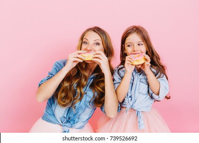 Portrait of happy young mother and daughter eating tasty donuts after dinner, isolated on pink background. Two adorable long-haired curly sisters baked delicious cupcakes together and tasted them.