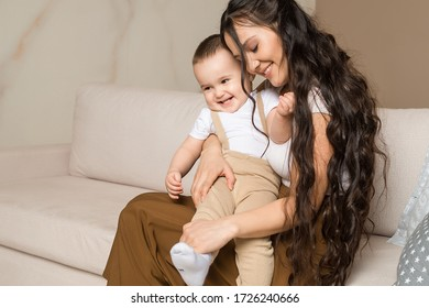 Portrait of happy young mother embracing her baby son. Brunette woman sitting on couch nursing her child. Childcare, family, motherhood