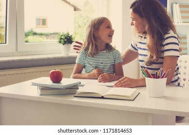 Portrait of happy young mother and her pretty little daughter sitting at the table and reading books