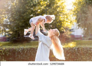 Portrait of happy young mother with little cute baby daughter spending time together in summer park. Happiness, happy parenting and childhood concept