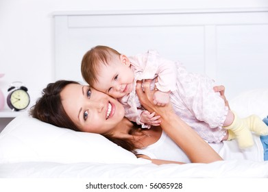 Portrait of happy young mother lying with her baby on the bed at home
