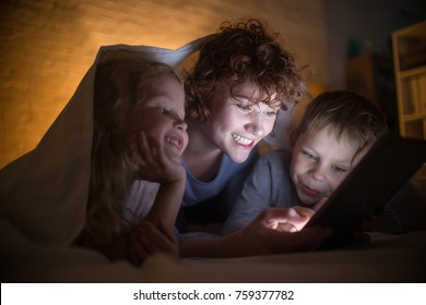 Portrait of happy young mother with two children reading stories in bed, hiding under blanket and using tablet