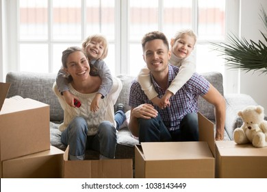 Portrait of happy young multinational family bonding together, smiling adopted kids embracing parents on couch with boxes on moving day, children hugging mother father looking at camera in new home