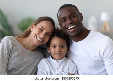Portrait of happy young multinational family with preschooler biracial boy child posing at home, smiling international parents and mixed race ethnicity little son look at camera enjoy time together