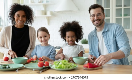 Portrait of happy young multiracial family with little children cook together in modern renovated kitchen, smiling multiethnic parents have fun preparing healthy food breakfast with small daughters