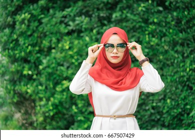 Portrait of happy young muslim woman red hijab over blurred the green field  background.