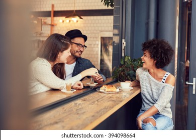 Portrait of happy young people sitting together at a cafe having some food and coffee. Group of friends meeting in a coffee shop.