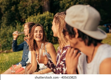 Portrait of happy young people sitting by a lake with beers. Group of friends hanging out at the lake.