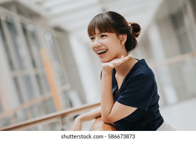 Portrait of happy young pretty Asian girl with braces smiling.
