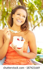 Portrait of a happy young pretty mixed race woman enjoying frozen yogurt with blueberry and strawberry fruit toppings outside. Vertical shot.