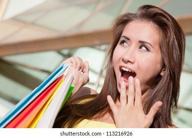 Portrait of happy young shopper surprised sales