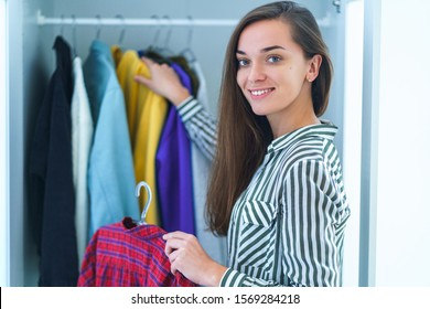 Portrait of happy young smiley brunette woman choosing outfit from wardrobe closet with stylish clothes and home stuff