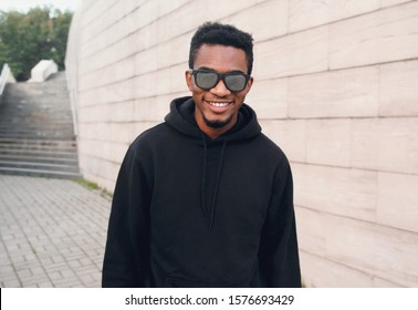 Portrait happy young smiling african man wearing black hoodie, sunglasses on city street