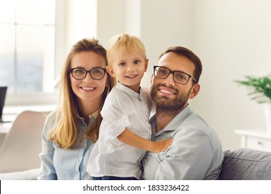 Portrait of happy young smiling family sitting, holding little son on knees and looking at camera together at home with room interior at background. Happy family and childhood concept