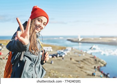 portrait of happy young smiling woman in warm clothing and knitted red hat with orange backpack in Ice Lagoon in Iceland with background of sea and sky. a woman is showing Victory sign with a happy