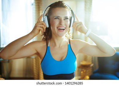 Portrait of happy young sports woman in fitness clothes listening to the music with headphones in the modern house.