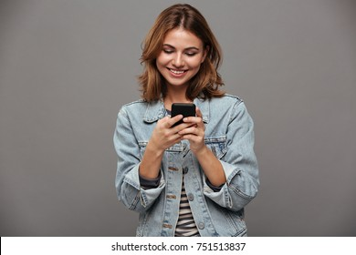 Portrait of a happy young teenage girl dressed in denim jacket using mobile phone isolated over gray background