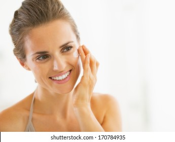 Portrait of happy young woman applying cream in bathroom