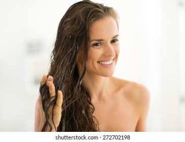 Portrait of happy young woman applying hair mask in bathroom
