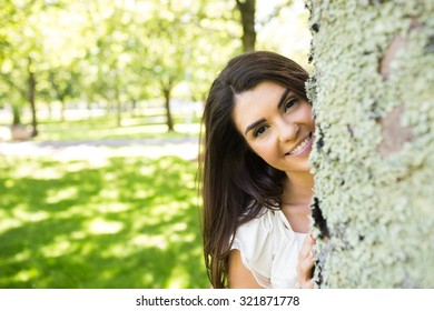 Portrait of happy young woman behind tree trunk in park