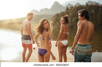 Portrait of happy young woman in bikini looking over her shoulder and walking with her friends on jetty. Group of young people walking together on a pier at the lake on a sunny day.