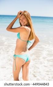 Portrait of happy young woman in bikini standing on beach