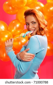 portrait of happy young woman biting candy over balloons