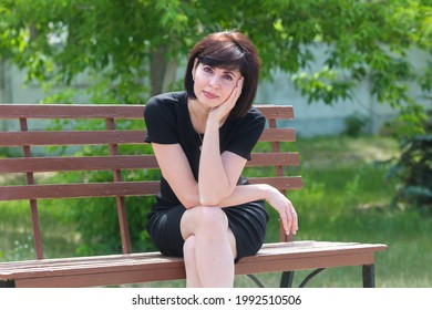 Portrait of a happy young woman in black dress on a bench in the park. - Shutterstock ID 1992510506