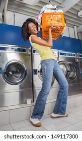Portrait of happy young woman carrying heavy basket of clothes in laundromat