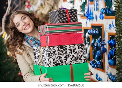 Portrait of happy young woman carrying stacked gift boxes in Christmas store