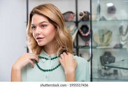 Portrait of happy young woman choosing greenstone bead necklace in shop