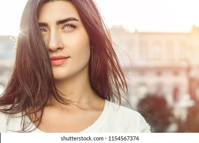 Portrait of a happy young woman. Close-up of a smiling girl with clean skin. Female with beautiful eyes and hair outside. Student. Copy space.