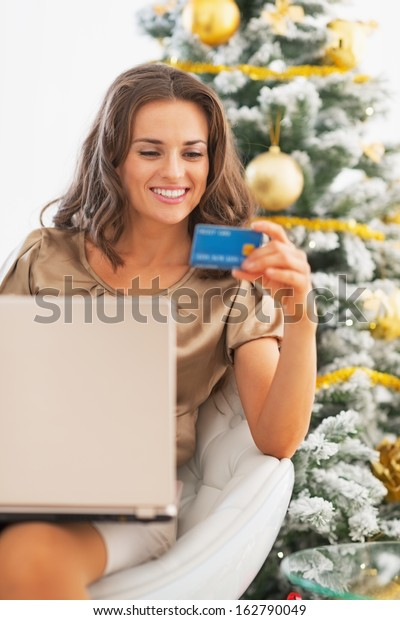 Portrait of happy young woman with credit card using laptop near christmas tree