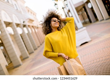 Portrait of happy young woman with  curly hair holding a lot of shopping bags with gifts outdoors