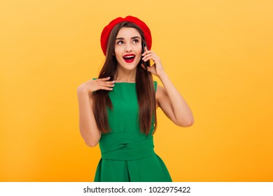 Portrait of a happy young woman dressed in beret and green dress talking on mobile phone isolated over yellow background
