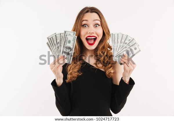 Portrait of a happy young woman dressed in black dress holding bunch of money banknotes isolated over white background