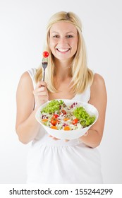 Portrait of happy young woman eating fresh vegetable.