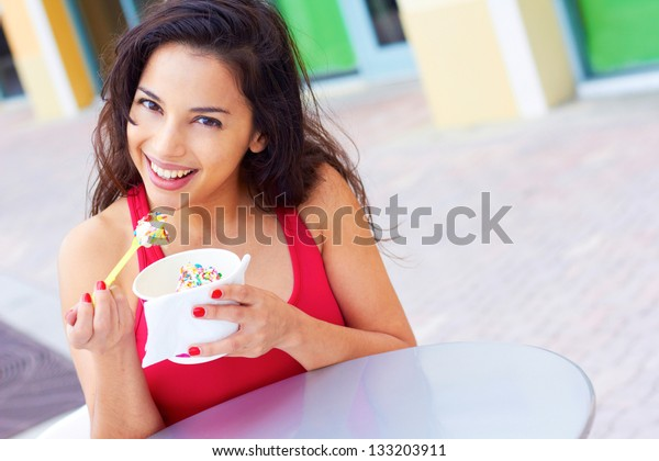 Portrait of a happy young woman enjoying frozen yogurt at cafe table. Horizontal shot.