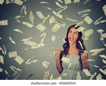 Portrait happy young woman exults pumping fists ecstatic celebrates success under a money rain falling down dollar bills banknotes isolated on gray wall background with copy space