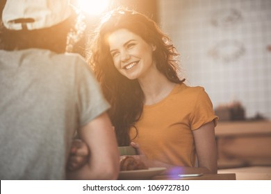 Portrait of happy young woman having breakfast with her boyfriend in cafeteria. She is looking at man with love and smiling