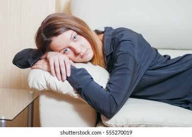 Portrait of the happy young woman having a rest on a bed at home