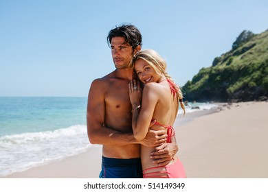 Portrait of happy young woman with her boyfriend on the sea shore. Loving couple on the beach enjoying summer holidays.