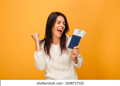Portrait of a happy young woman holding traveling tickets and passport isolated over yellow background