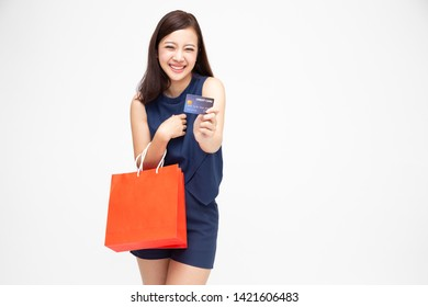 Portrait of a happy young woman holding shopping bags and credit card isolated over white background, Year end sale or mid year sale promotion clearence for Shopaholic concept, Asian female model