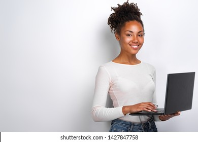 Portrait of happy young woman holding laptop computer over white background