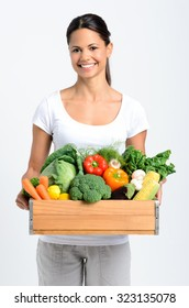 Portrait of happy young woman holding a crate full of fresh organic vegetables on grey background, promoting healthy diet and lifestyle