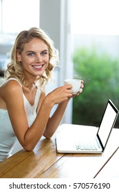 Portrait of happy young woman holding coffee cup at home