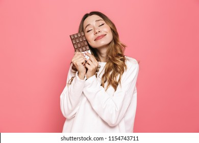 Portrait of a happy young woman hugging chocolate bar isolated over pink background