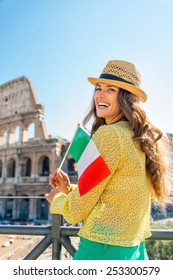 Portrait of happy young woman with italian flag in front of colosseum in rome, italy